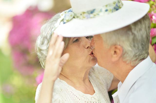 Casal idoso dando beijo