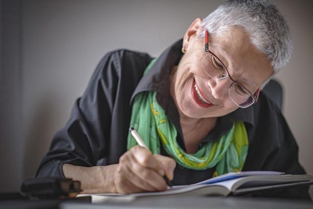 Mulher idosa escrevendo